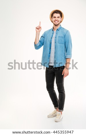 Happy young man pointing finger at copyspace over white background - stock photo