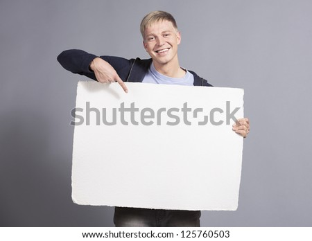 Happy young man pointing finger at white empty signboard with space for text while holding it isolated on grey background. - stock photo