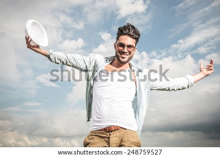 Happy young man posing outdoor with his arms open, enjoying the sunny weather. - stock photo