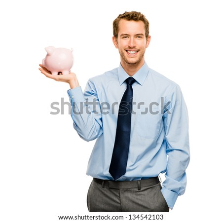 Happy young man putting money in piggy bank isolated on white - stock photo