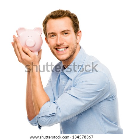 Happy young man putting money in piggy bank isolated on white background - stock photo