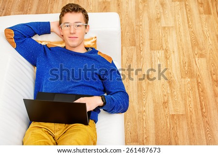 Happy young man resting on a sofa with a laptop on his knees.  - stock photo