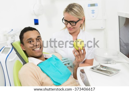 Happy young man sitting in the dentist's chair and holding a green apple at dentist's office. Young lady woman smiling to him. - stock photo