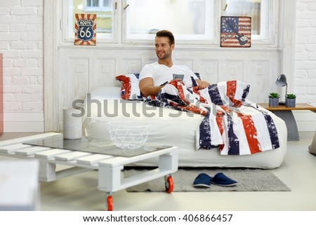 Happy young man smiling in bed, holding morning tea, looking away. - stock photo