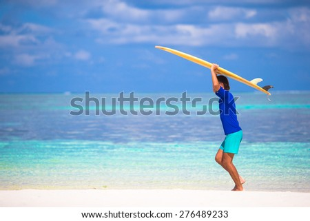 Happy young man surfing on the tropical coast - stock photo