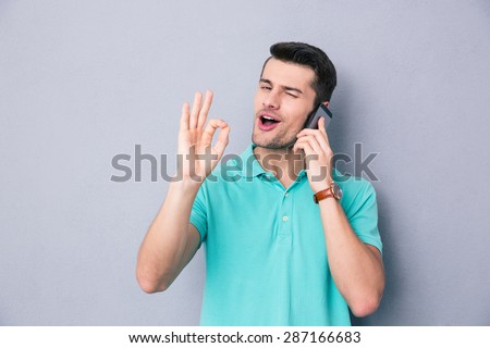 Happy young man talking on the phone and gesturing ok sign over gray background - stock photo