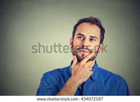 Happy young man thinking daydreaming looking up isolated on gray wall background  - stock photo