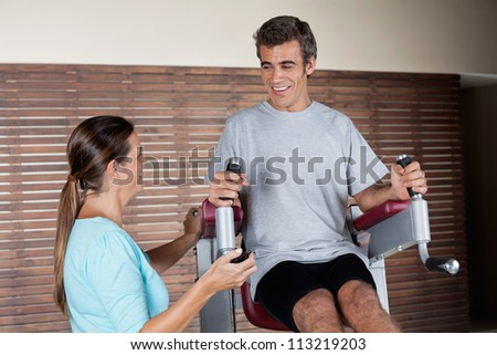 Happy young man using an exercise machine while looking at instructor in health club - stock photo