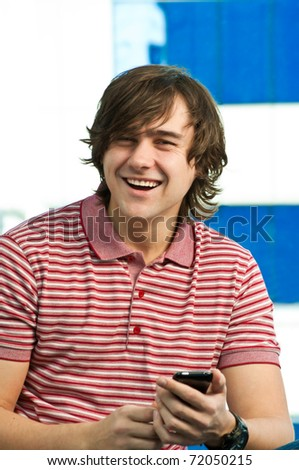 Happy young man using mobile phone, looking at camera - stock photo