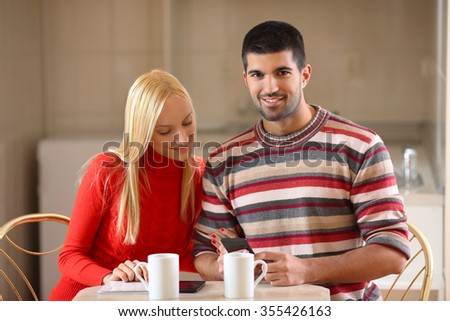 Happy young man using smart-phone while having a cup of coffee with his girlfriend at home - stock photo