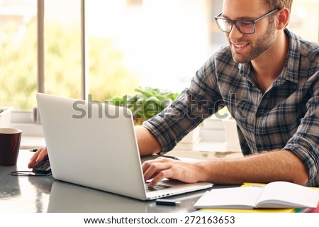 Happy young man, wearing glasses and smiling, as he works on his laptop to get all his business done early in the morning with his cup of coffee - stock photo