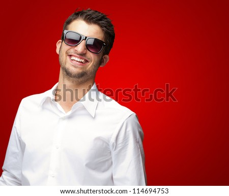 Happy Young Man Wearing Glasses On Red Background - stock photo
