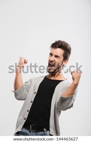 Happy young man with arms up, over a gray background - stock photo