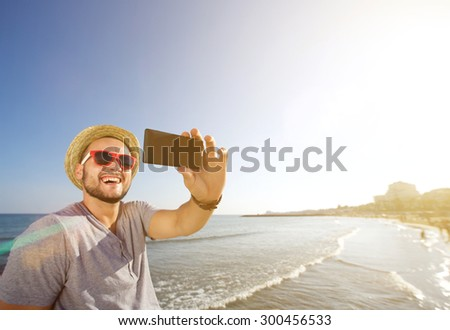 Happy young man with hat taking selfie at the beach - stock photo