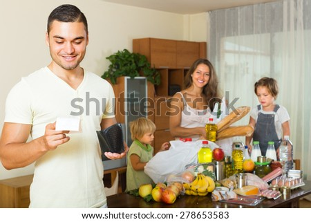 Happy young man with receipt from store, family brought food home