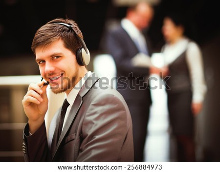 Happy young man working at callcenter, using headset - stock photo