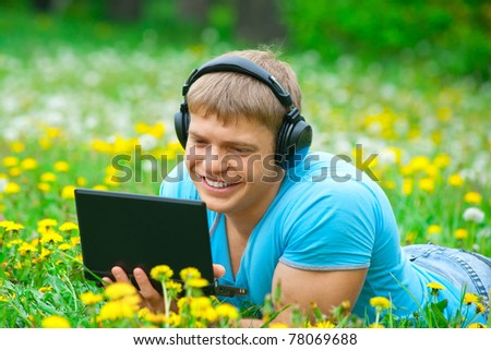 Happy young man working with a laptop and listening music on headphone outdoors - stock photo