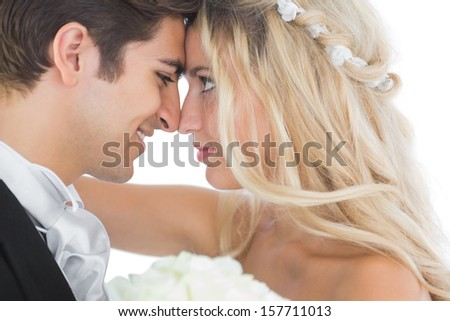 Happy young married couple looking each other in the face on white background - stock photo