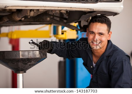 Happy young mechanic draining engine oil at an auto shop for an oil change - stock photo
