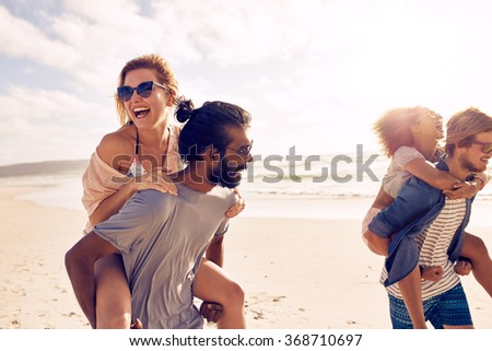 Happy young men giving piggyback ride to women on beach. Diverse group of young people having fun on the beach and piggybacking. - stock photo