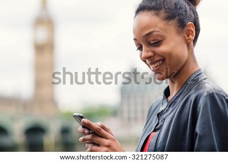 Happy young mixed race businesswoman portrait outdoors in London with Big Ben as background while using smartphone to send a text message. Filtered image. - stock photo