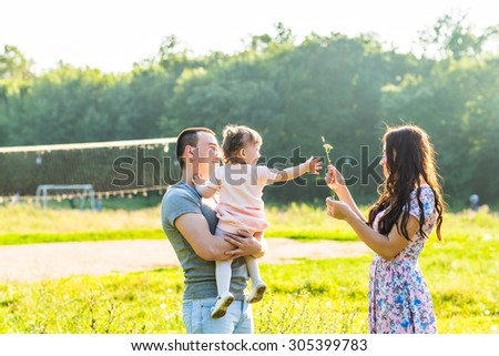 Happy Young Mixed Race Ethnic Family Walking In The Park. - stock photo