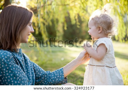 Happy young mom and adorable blond girl playing together in park in summertime, smiling mother holding her little daughter hand, supporting her first steps, looking at baby with adoration - stock photo