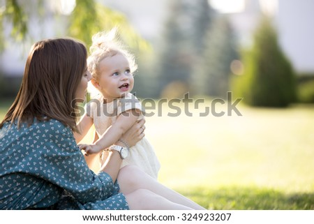 Happy young mom and adorable blond girl playing together in park in summertime, smiling mother holding her little daughter in arms, talking, looking at baby with love and adoration, copyspace - stock photo