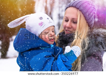 Happy  young mother and baby playing in winter park  - stock photo