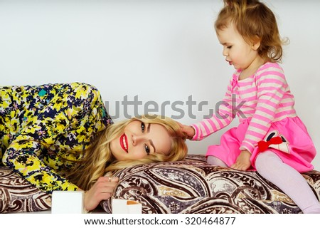 Happy young mother and daughter playing - stock photo