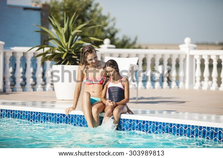 Happy young mother and daughter sitting on the edge of a swimming pool - stock photo