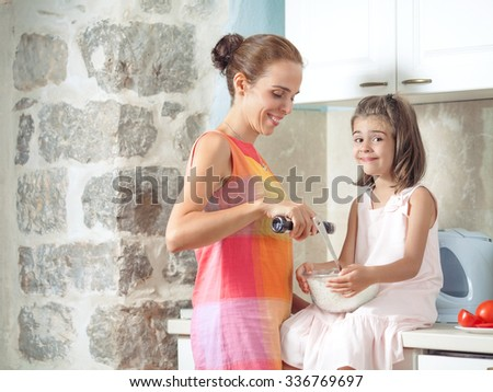 Happy young mother and her cute little daughter preparing healthy meal in the kitchen - stock photo