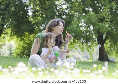 Happy young mother and her daughter blowing soap bubbles in park - stock photo