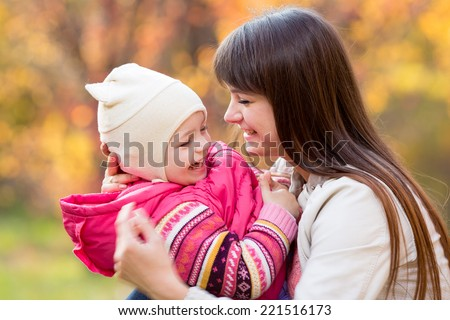 happy young mother and her daughter child have fun sitting at fall background - stock photo
