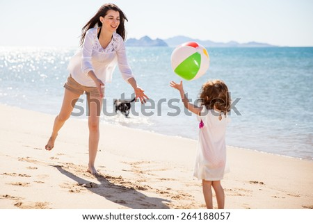 Happy young mother and her daughter playing with a beach ball on a sunny day - stock photo