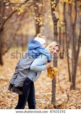 happy young mother and her son spending time in the autumn park (focus on the woman) - stock photo