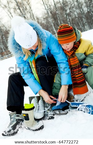 happy young mother and her son tightening laces and getting ready to go ice-skating - stock photo