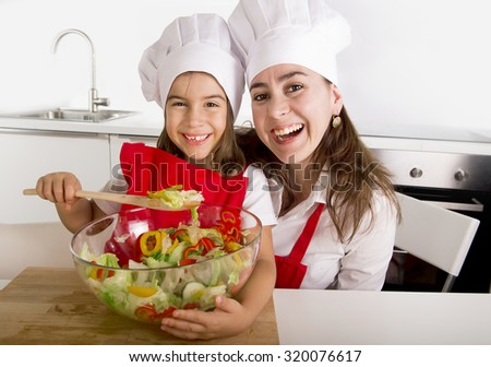 happy young mother and little daughter at home kitchen having fun preparing salad bowl wearing apron and cook hat playing together in healthy vegetables nutrition education concept - stock photo
