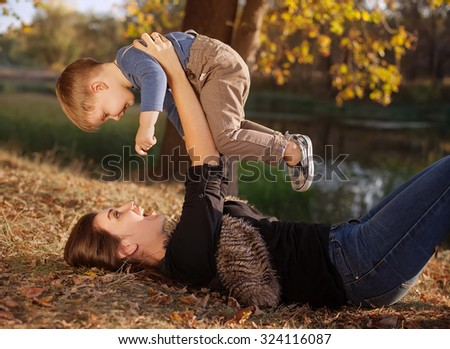 Happy young mother and  son having fun outdoor  autumn day - stock photo