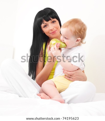 happy young mother feeding her baby with fruit  on the bed at home - stock photo