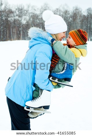 happy young mother going ice skating with her little son - stock photo