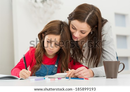 Happy Young Mother Helping Her Daughter While Studying At Home - stock photo