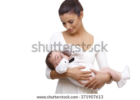 Happy young mother holding baby boy dressed in shirt and bow tie, drinking from feeding bottle. - stock photo