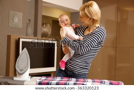 Happy young mother holding little baby in arm, ironing at home. - stock photo