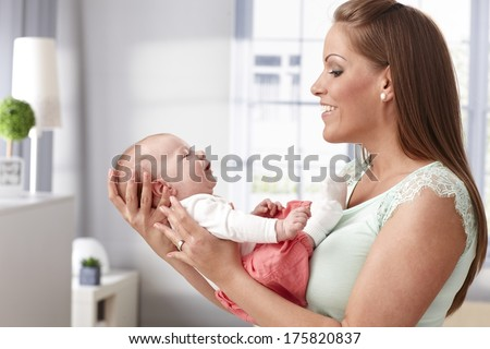 Happy young mother holding newborn baby girl in arms, smiling to her. - stock photo