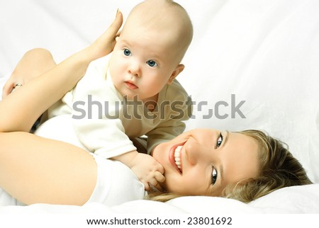 happy young mother lies on the white sofa with her four months old baby - stock photo