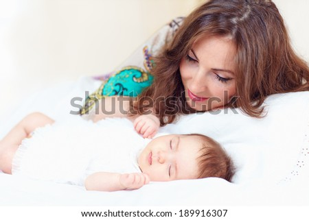 happy young mother near sleeping baby girl - stock photo