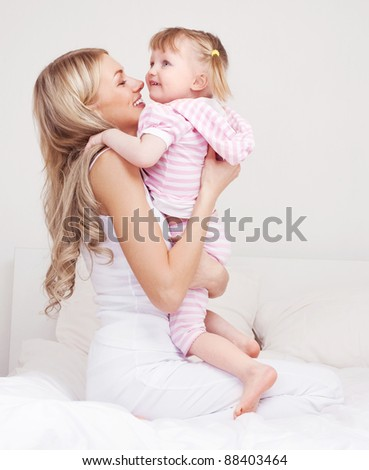 happy young mother playing with her daughter on the bed at home (focus on the woman) - stock photo