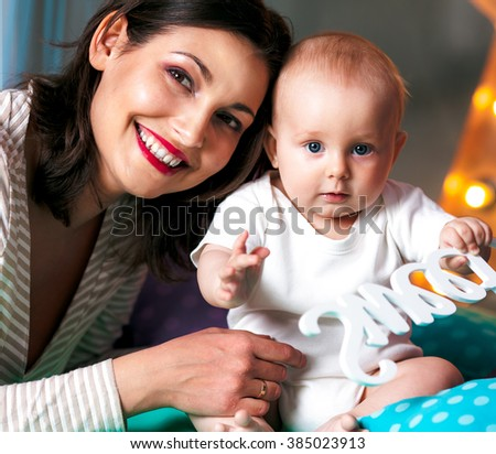 Happy young mother playing with little baby on white background - stock photo