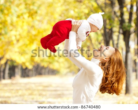 Happy young mother playing with little daughter in autumn park - stock photo